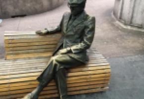 André l'Huillier, assis sur un banc à côté du kiosque à journaux, DR